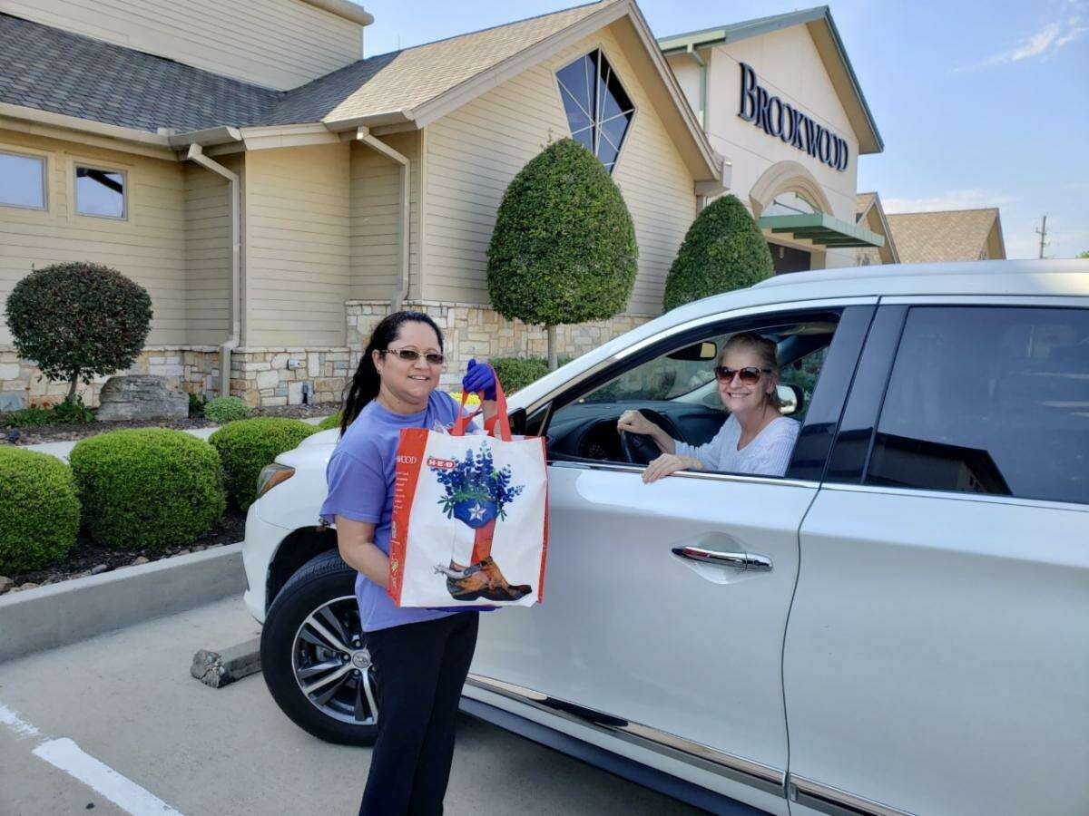 A happy customer picks up curbside takeout from the Brookwood Café in Brookshire. The food ordered from the special to-go menu supports The Brookwood Community's citizens during the COVID-19 pandemic.