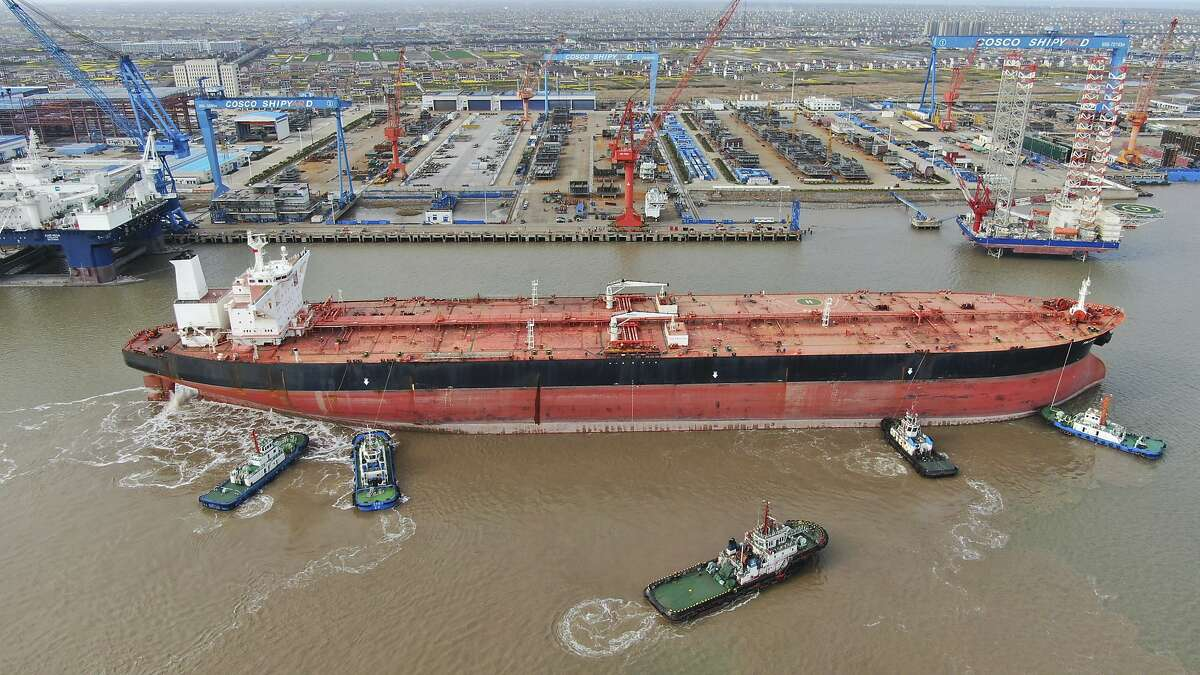 FILE - In this photo taken Monday, March 16, 2020, tugboats push a 300,000-ton very large crude carrier (VLCC) to a shipyard on the Yangtze River for retrofit in Qidong city in east China's Jiangsu province China.