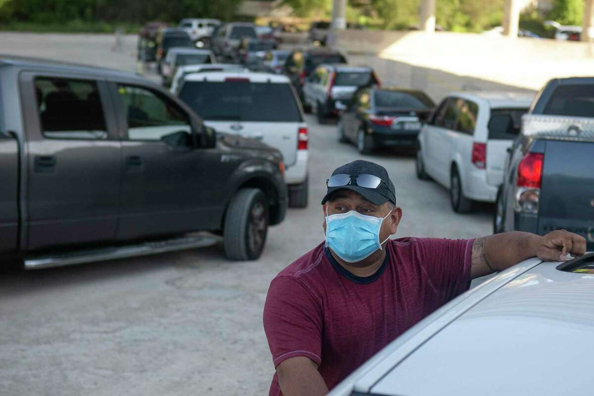 Gabriel Sanchez stands outside his car before the April 24, 2020 San Antonio Food Bank drive thru food distribution at Toyota Field in San Antonio, Texas. Sanchez had been waiting in line since 7 a.m. for the 10 a.m. distribution.