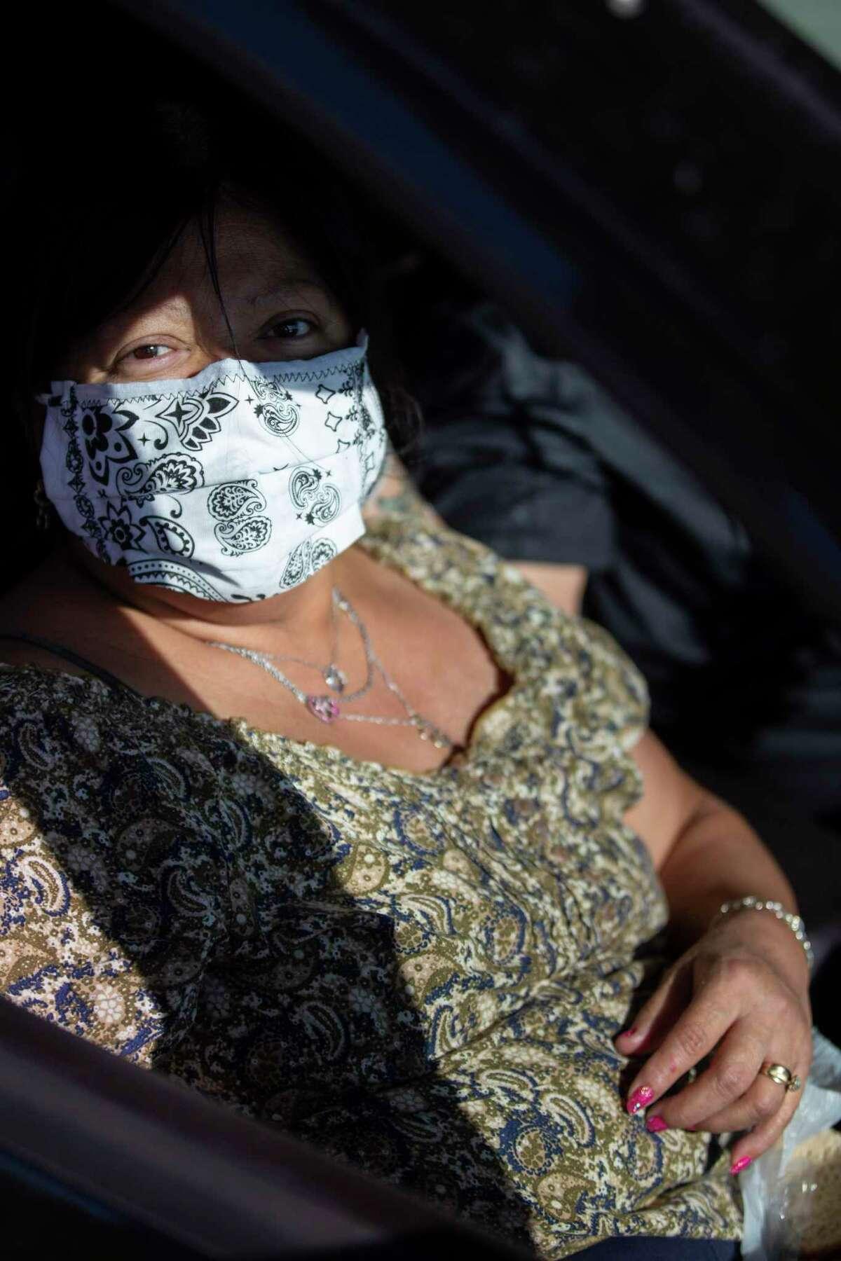 Anita Rodriguez poses wearing her mask in her car before the April 24, 2020 San Antonio Food Bank drive thru food distribution at Toyota Field in San Antonio, Texas.