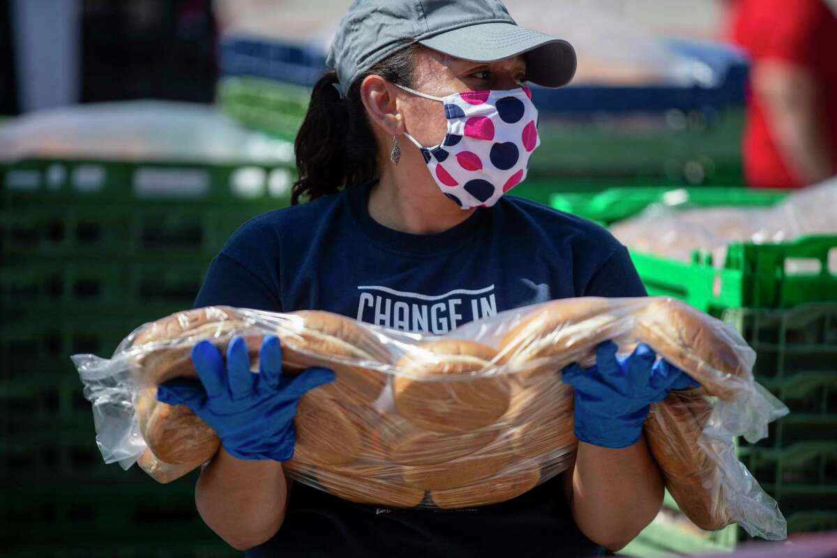Elizabeth Davila holds a package of buns to give out during the April 24, 2020 San Antonio Food Bank drive thru food distribution at Toyota Field in San Antonio, Texas.