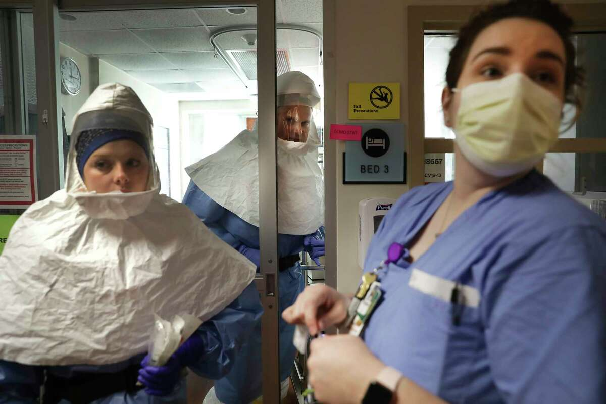 Nurse Keri Ginger, left, and Dr. Charles Burch, center, and another nurse wait to intubate a patient at Methodist Hospital's COVID-19 unit on April 23, 2020.
