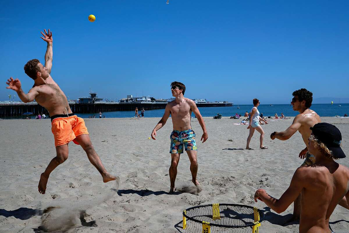 Santa Cruz High School Spike Ball Club members, from left to right, Quinn Cury, 18, Shelby Durkee 18, Justin Cowen, 18, and Lachlan Nagel, 16, play Spike Ball on Cowell Beach on Wednesday, April 22, 2020 in Santa Cruz, Calif. The club has been to the beach every day since Santa Cruz opened them.