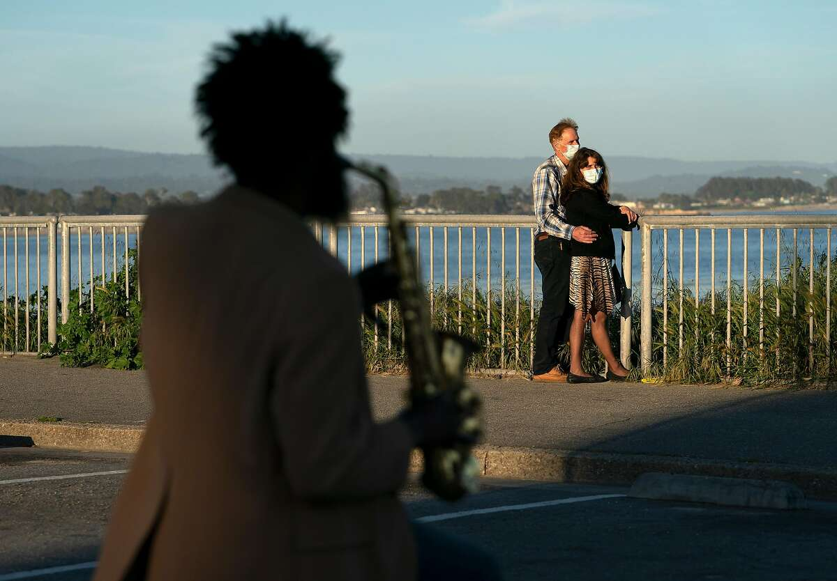 Tatiana Milwee and David Rasmussen listen to Tony Street play the saxophone near Steamer Lane along W. Cliff Dr. on Wednesday, April 22, 2020 in Santa Cruz, Calif.
