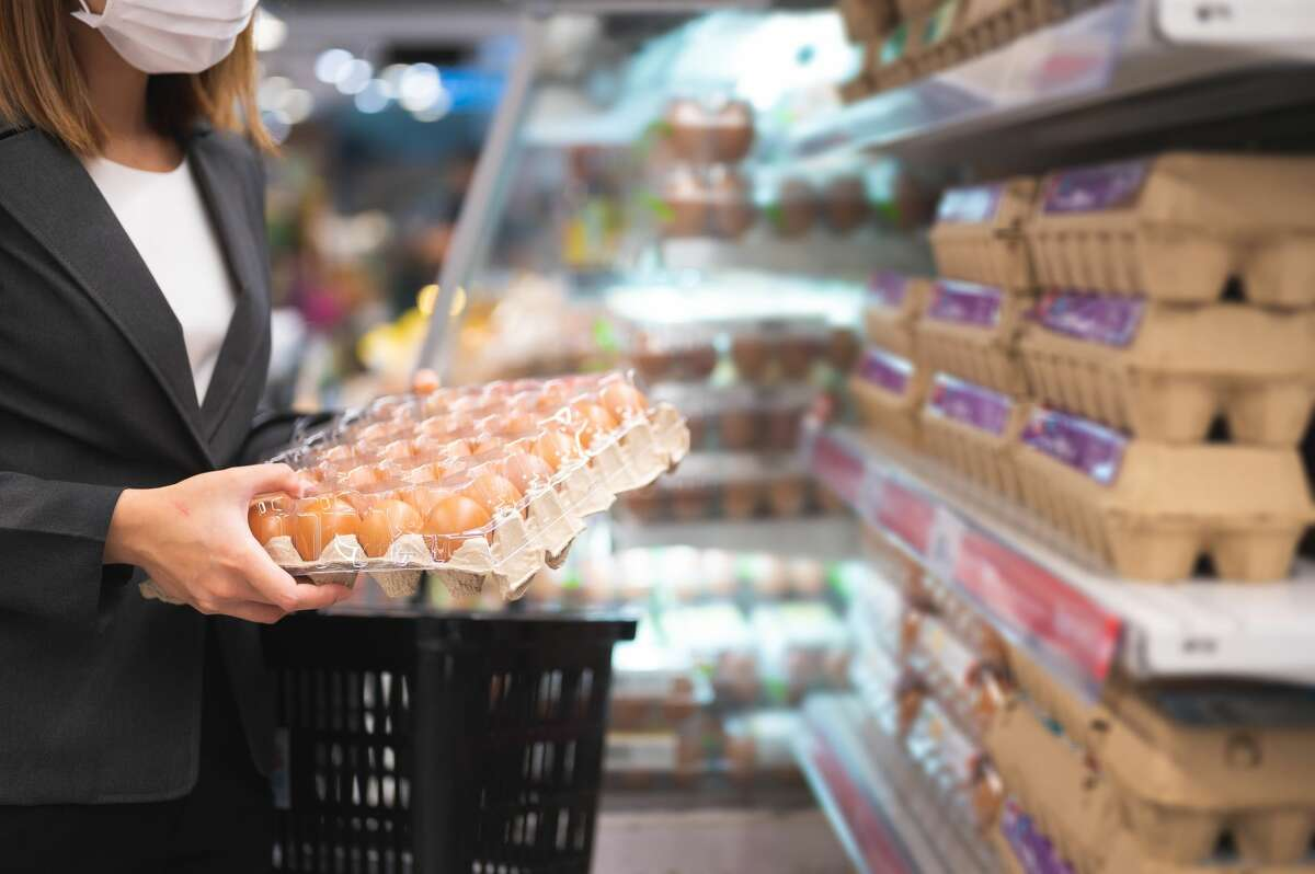 Woman buying eggs while coronavirus or COVID-19 spreading situation