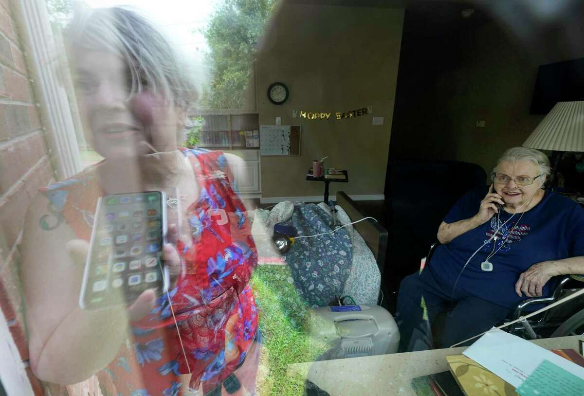 Cathy Lester is reflected in the window as she speaks on the phone to her mother, Ann Criswell, a resident at The Waterford at College Station, 1103 Rock Prairie Rd., Sunday, April 19, 2020, in College Station. A majority of the residents have tested positive for COVID-19.