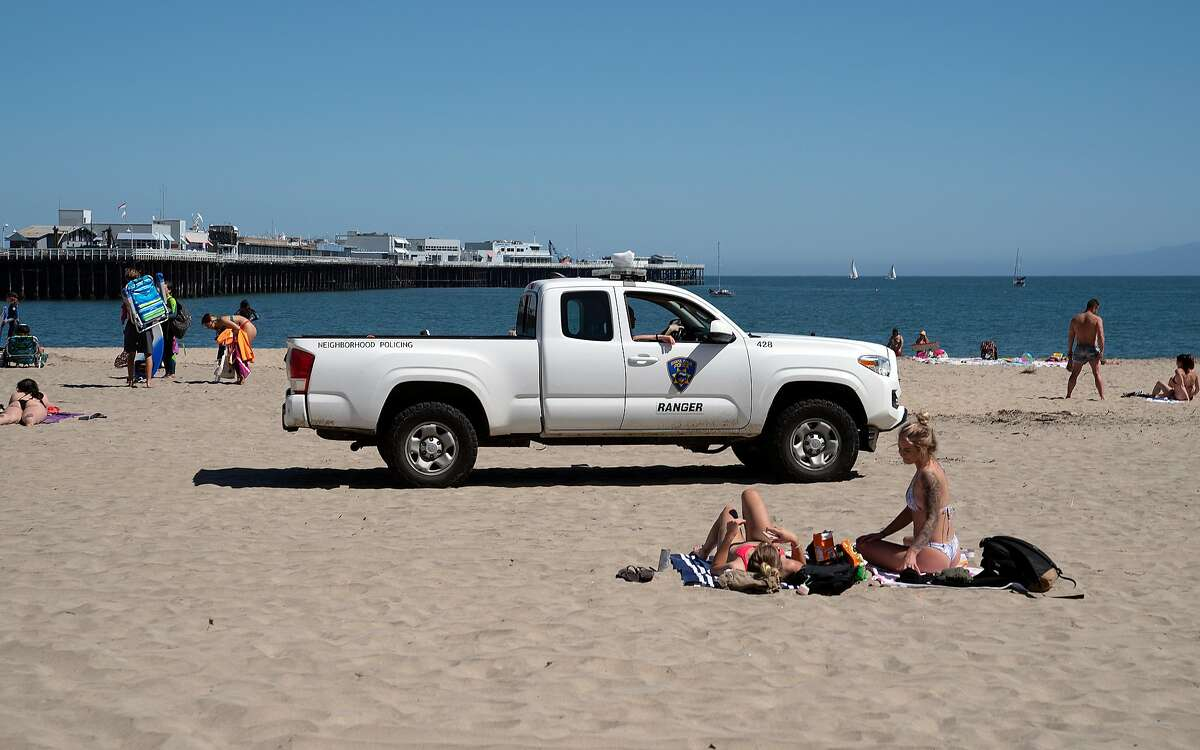 Santa Cruz Police Department officers tell beach goers that the beach is only open to people who are exercising on Wednesday, April 22, 2020 in Santa Cruz, Calif.