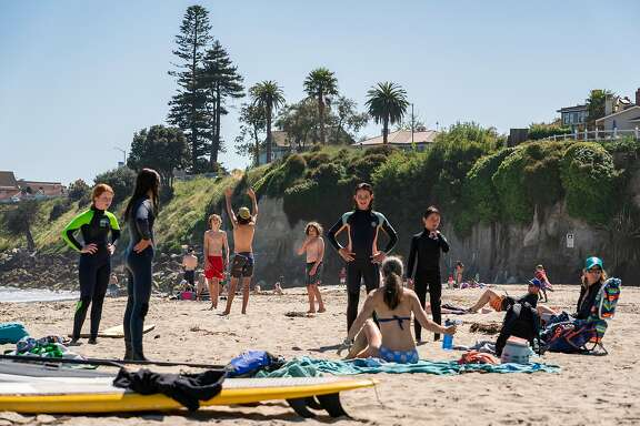 Surfers get ready to surf at Cowell Beach on Wednesday, April 22, 2020 in Santa Cruz, Calif.