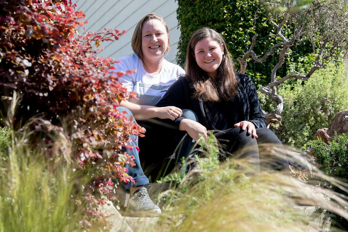 (From left) Jamie and Tarah Burns pose for a portrait outside of their home in San Francisco, Calif. Thursday, April 23, 2020. After years of waiting, they were scheduled to undergo fertility treatments to get pregnant this spring. But the coronavirus pandemic closed fertility clinics and has delayed their treatment indefinitely. They've gone from expecting to be pregnant in 6 weeks to not knowing when they'll be able to build their family.
