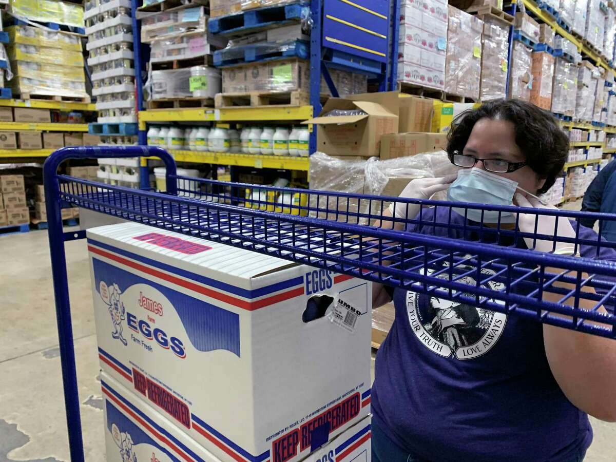 Jennifer Aghassibake dons a mask as she buys eggs and other items at the Restaurant Depot on Fredericksburg Road. She has been delivering eggs to friends and others to as far away as Austin during the coronavirus pandemic.
