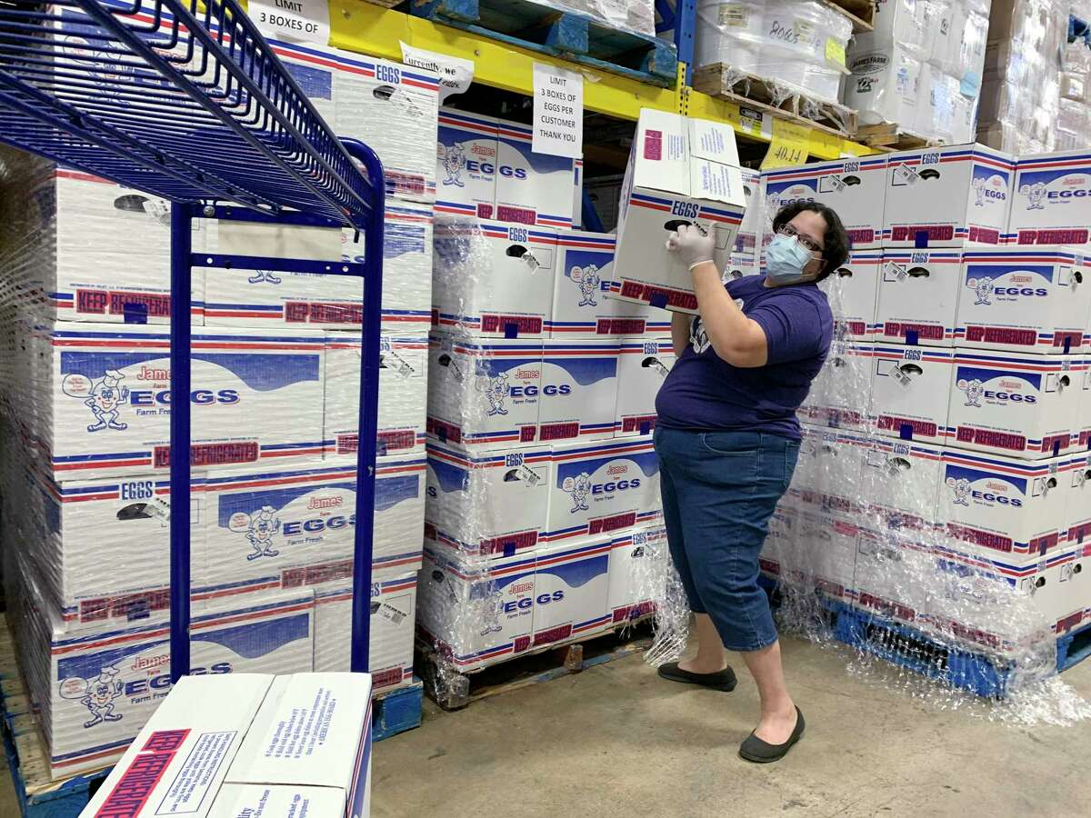 Jennifer Aghassibake loads boxes of eggs on her cart at the Restaurant Depot, a wholesale supply store. She first noticed the store had an abundance of eggs at a time when grocery store shelves were emptying of staples.