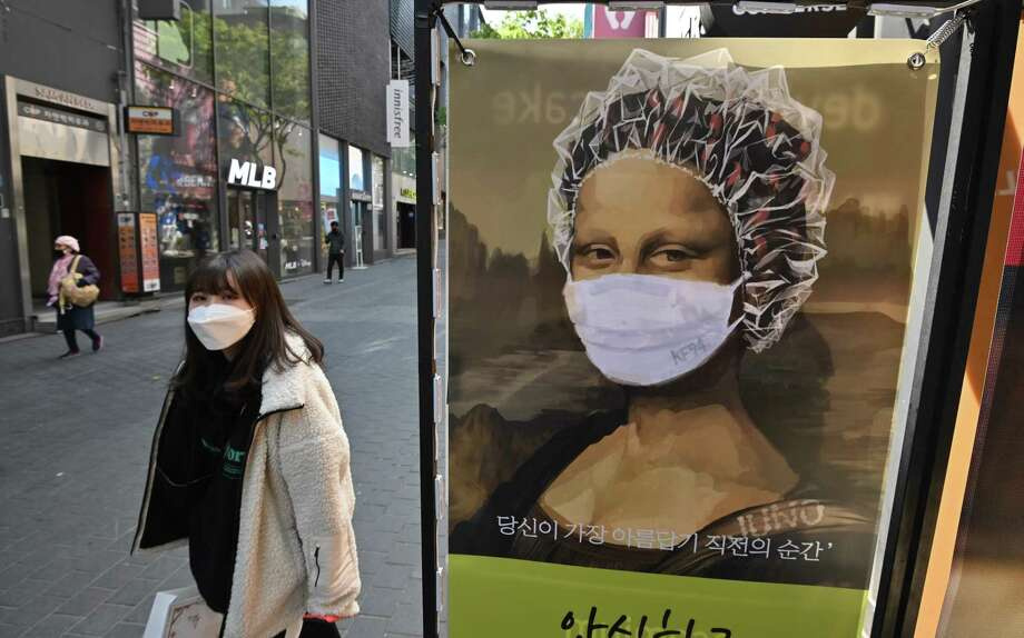 A woman wearing a face mask walks past an advertisement of a hair shop at a shopping district in Seoul on April 23. Photo: Jung Yeon-Je / AFP Via Getty Images / AFP or licensors