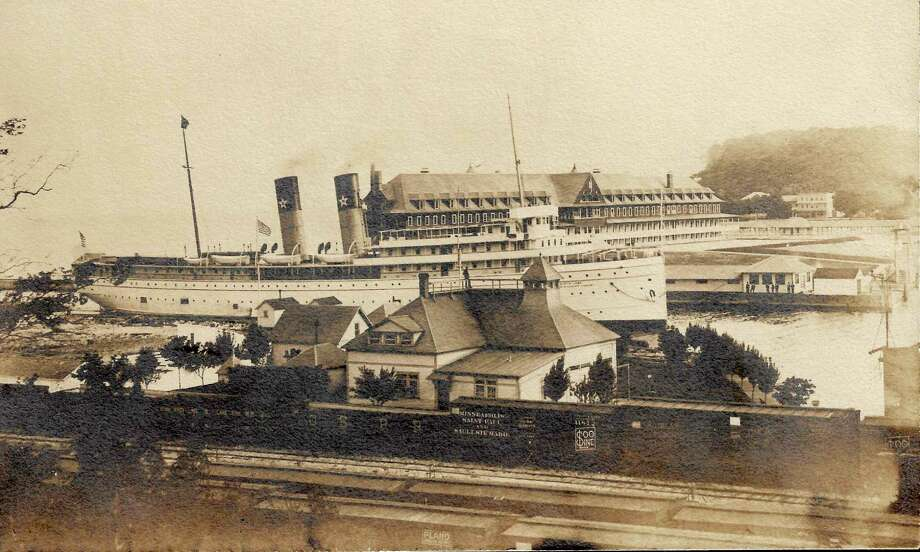 """A view of the busy Frankfort/South Frankfort harbor entrance in 1906, including cars and tracks of the Ann Arbor carferry yards, the South Frankfort Lifesaving Service building (note surfman on roof on watch), thepassenger steamer """"Northland"""" approaching the Frontenac Hotel dock (the long, low building off the ship's bow is the Frontenac's bowling alley, now the American Legion Hall), and in the far background the Delbridge House Hotel on Main Street. (Courtesy Photo)"""