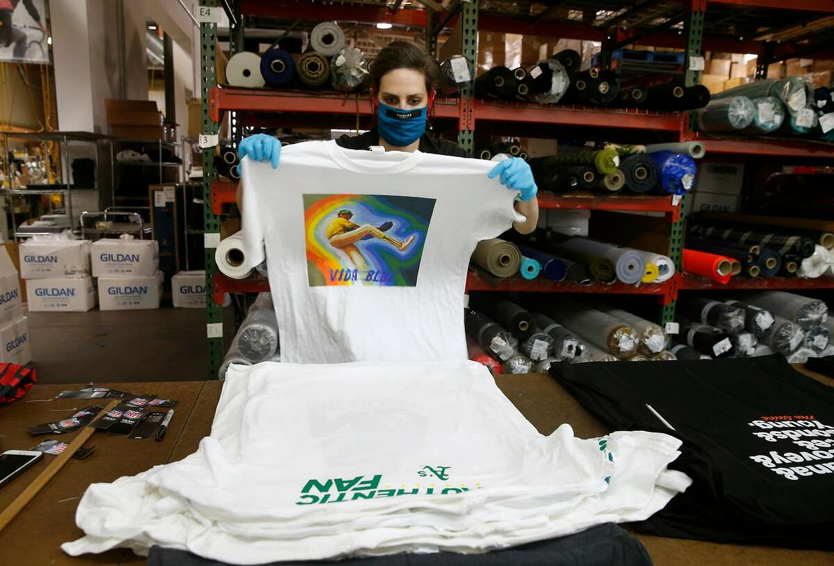 Emily Raimondi, from NBC Sports Bay Area and California, sorts t-shirts that will be used to make face masks at the Timbuk2 factory in San Francisco, Calif. on Tuesday, April 21, 2020. Timbuk2 is suspending production of its popular messenger bags and is teaming up with NBC Sports Bay Area and California to manufacture face masks for medical workers from surplus apparel donated by seven local professional sports teams.