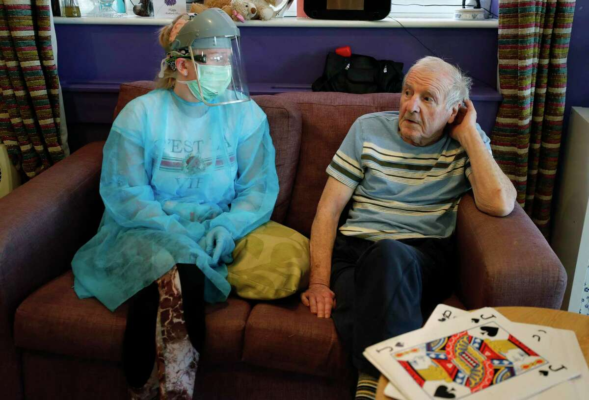 Across the world, including in Connecticut, nursing home workers are struggling to cope with the toll of caring for a vulnerable population during a pandemic. A workers' union said Friday that Connecticut officials are not doing enough to address employee safety. In this April 20, 2020, photo, a nurse sits beside a resident in the red zone where those sick with coronavirus stay at Wren Hall nursing home the central England village of Selston.
