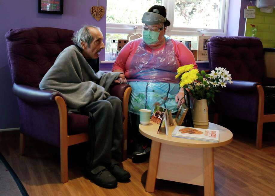 "Across the world, including in Connecticut, nursing home workers are struggling to cope with the toll of caring for a vulnerable population during a pandemic. A workers' union said Friday that Connecticut officials are not doing enough to address employee safety. A nurse sits beside a resident in the ""red zone"" at Wren Hall care home in the central England village of Selston on April 20, 2020. Photo: Frank Augstein / Associated Press / Copyright 2020 The Associated Press. All rights reserved"