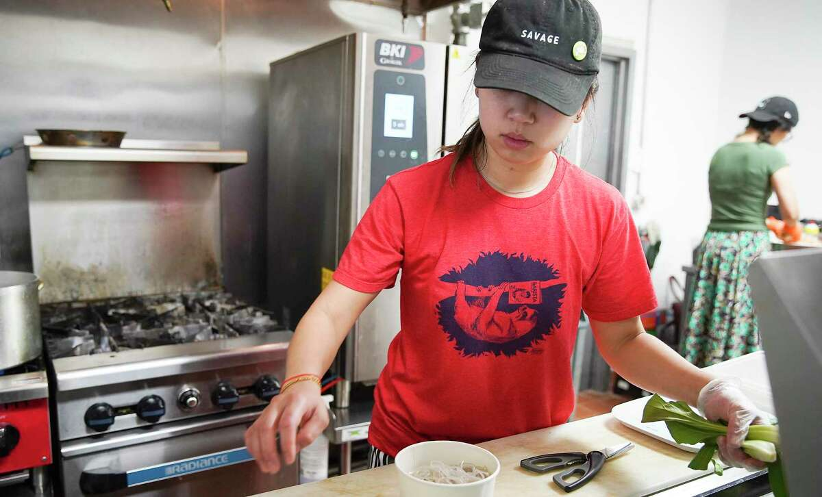 Amiley Lia preps an order as her mom, Elaine Won, makes dumplings at Dumpling Haus HTX in Sawyer Yards in Houston on Tuesday, March 17, 2020. Food service industry workers are among those with the lowest rate of paid sick leave coverage in the U.S.