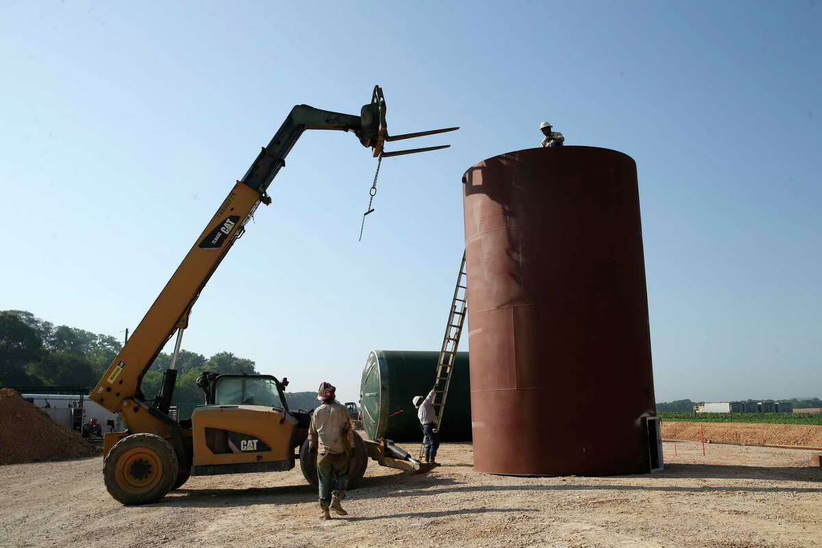 A roustabout crew works on a setting up oil containers at a drilling site by Millennium Exploration near Gonzales, Texas, Friday, April 24, 2020. They installed three tanks that hold 400 barrels of oil each and also a fiberglass tank for saltwater. The company drilled Chalk Talk #2 to a depth of 8,600 feet and went 4,000 feet horizontally. They expect 800 barrels a day from the well.