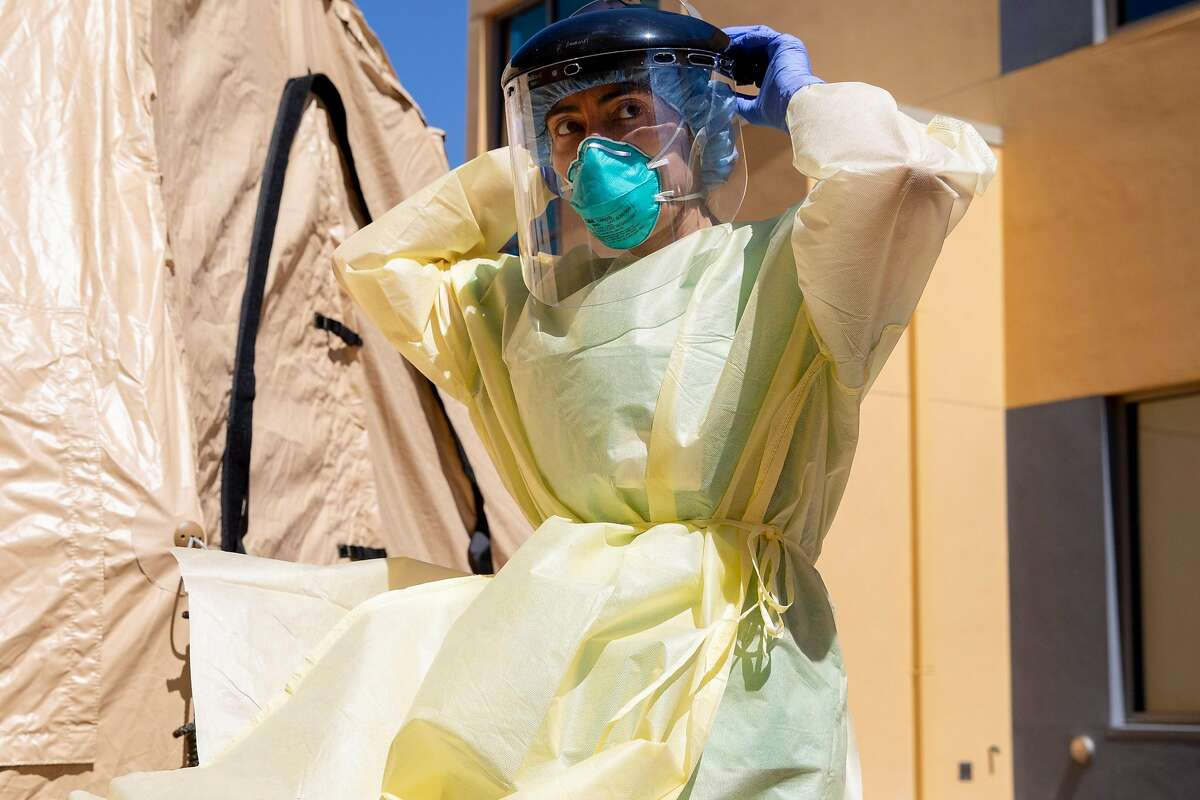 """Dr. Melina Beaton gears up in full personal protective equipment before administering a swab test on a patient at a walk-up Coronavirus testing site at West County Health Center in San Pablo, Calif. Friday, April 24, 2020. California Governor Gavin Newsroom Newsom says the state will need to test 60,000 to 80,000 each day in order to safely reopen society, with essential workers being tested more frequently than others. The state plans to open 86 new testing sites in """"testing deserts"""" in rural California and poor urban areas."""