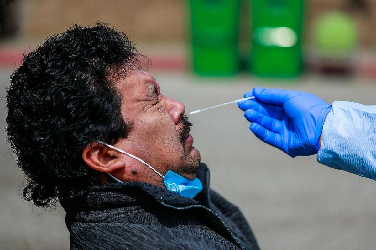 Dentist Dr. Marco Reyes (right) tests patient Refugio Rios (left) for Covid-19.