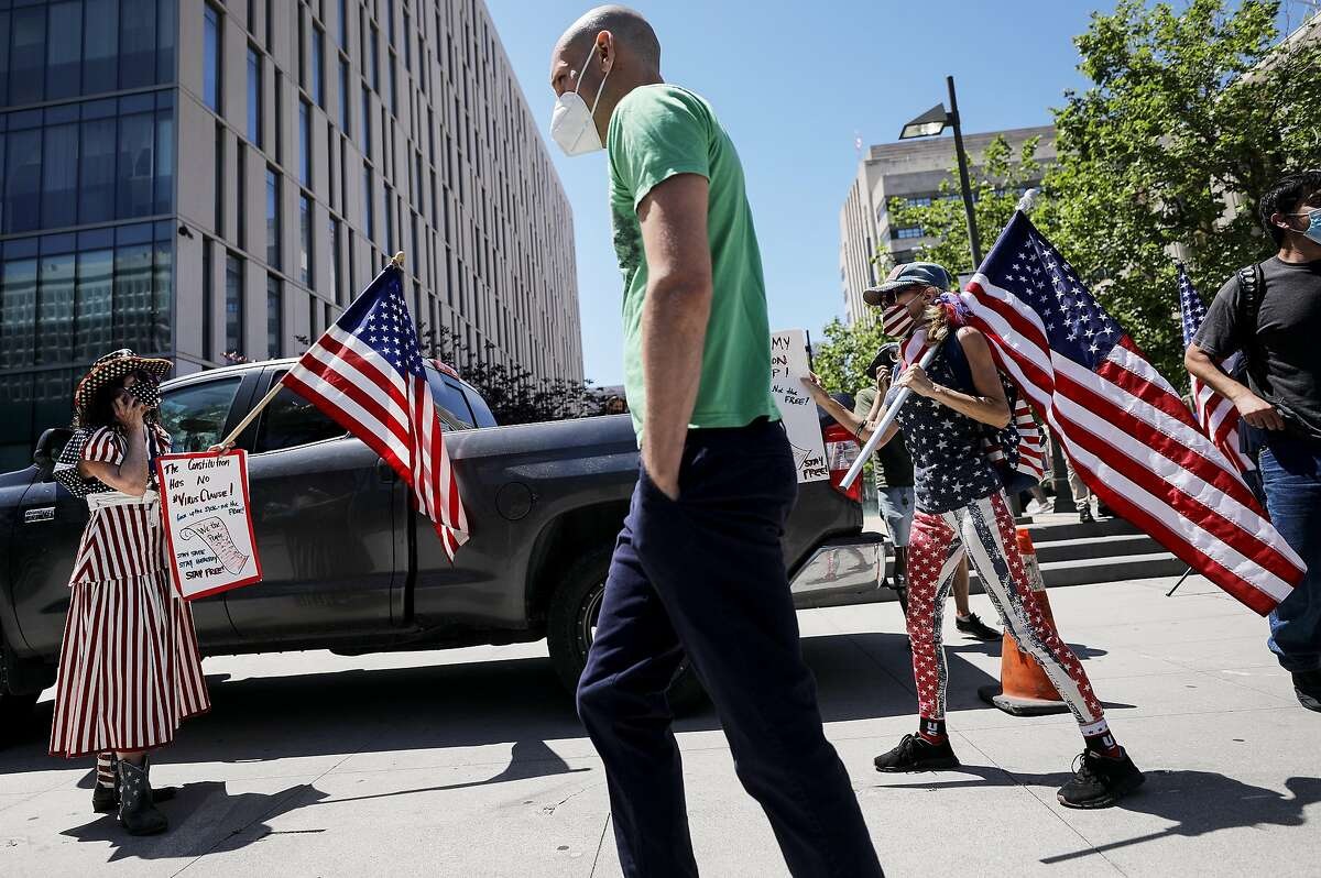 LOS ANGELES, CALIFORNIA - APRIL 22: Demonstrators hold U.S. flags as they participate in a protest outside City Hall calling on officials to re-open the economy amidst the coronavirus pandemic on April 22, 2020 in Los Angeles, California. A protest movement has sprung up in some states across the country calling for an end to shelter-at-home orders as the spread of COVID-19 continues. (Photo by Mario Tama/Getty Images)