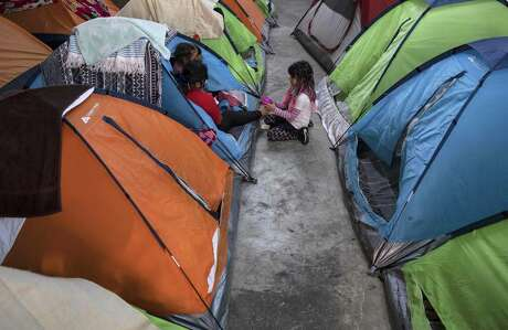 Members of an asylum-seeker family remain in a tent at the Juventud 2000 migrant shelter in Tijuana, Baja California State, Mexico, on April 3, 2020 during the novel coronavirus, COVID-19, pandemic. - Thousands of migrants overcrowding shelters or begging in the streets in Mexican cities along the US border are living in fear as the novel coronavirus spreads in the population and screening interviews for asylum seekers are being suspended. (Photo by Guillermo ARIAS / AFP) (Photo by GUILLERMO ARIAS/AFP via Getty Images)