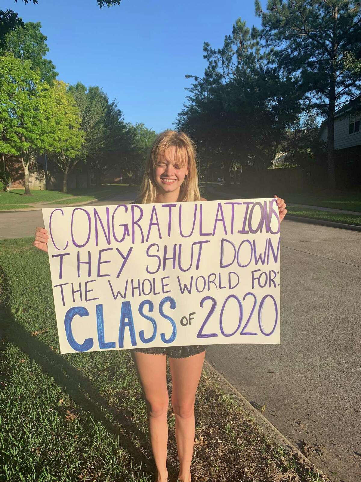 Neighbor Emma Neubauer holds a sign supporting Saddlebrook Crossing high school seniors during a special walking parade just for them in Katy on Thursday, April 23.