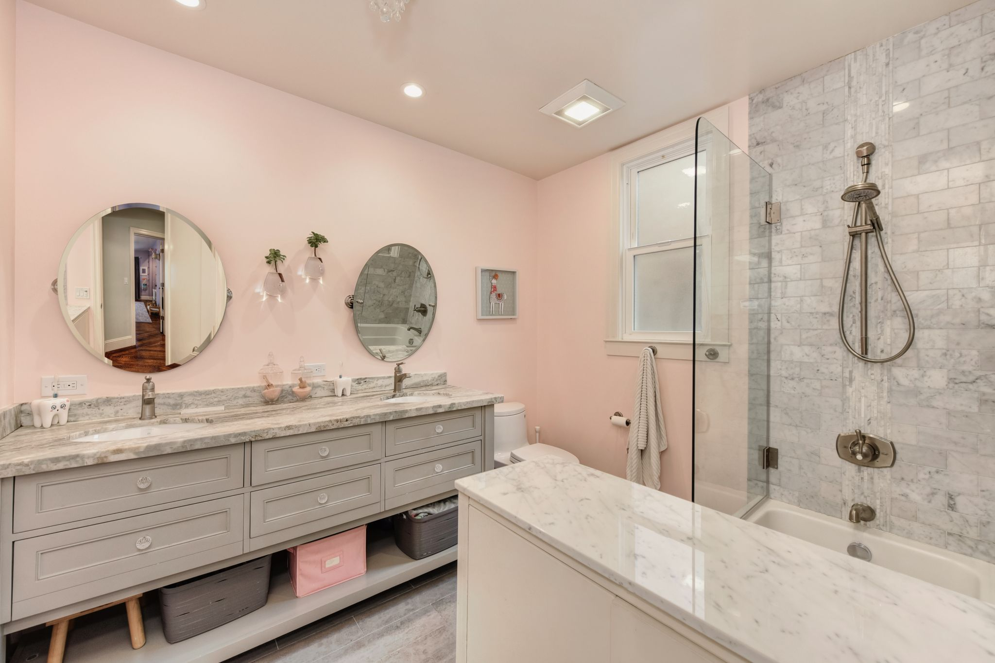 A bathroom with a shower tiled in marble is shared by the two other bedrooms.