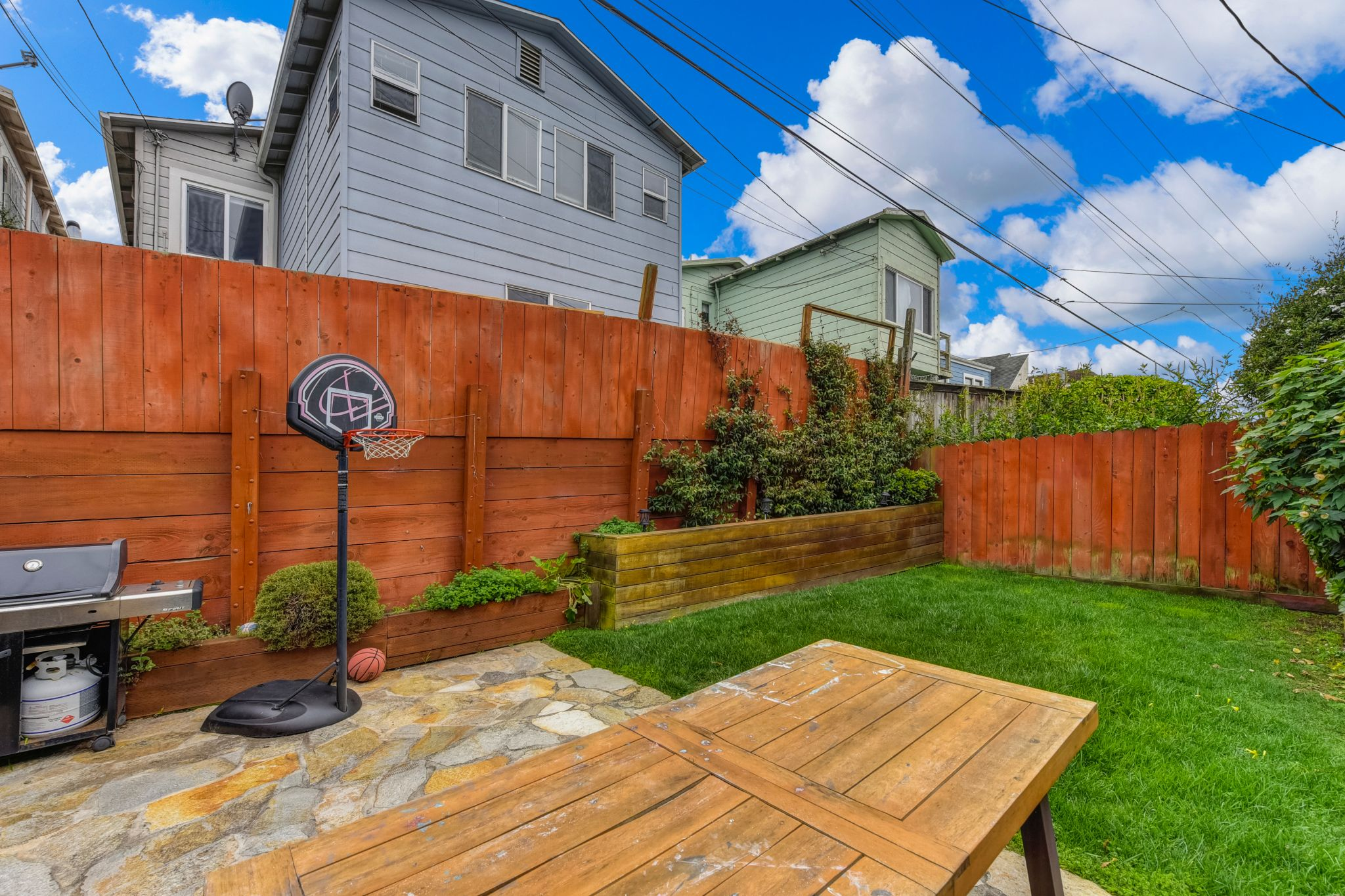 With a flagstone patio and a patch of grass, the backyard offers opportunities for outdoor play and dining.