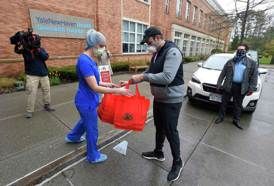 """Kim Jensen, a nurse in the surgical department at Greenwich Hospital accepts a food delivery from Paul DiPietro, of New Rochelle, N.Y. on Friday. Christopher Cassese, Vice President of Operations with Coughlin Insurance Services, arranged for the food donation that would help feed the 30 nurses working in the surgical department, who have been re-deployed to help with Covid-19 patients at the hospital. """"It's a way to brighten up their day,"""" Cassese said, through giving back to our frontline responders"""" referring to the lunches his company provided. Photo: Matthew Brown / Hearst Connecticut Media / Stamford Advocate"""
