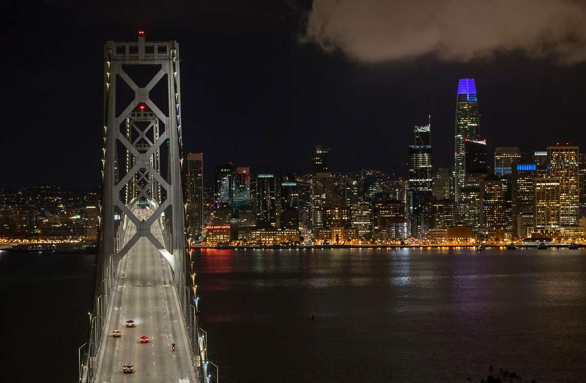 A few vehicles make their way across the Bay Bridge after midnight as the city shut down following an order to shelter in place in San Francisco, Calif., on Tuesday, March 17, 2020. The six Bay Area counties issued a shelter in place order for residents to try and curtail the spread of the Covid-19 virus.