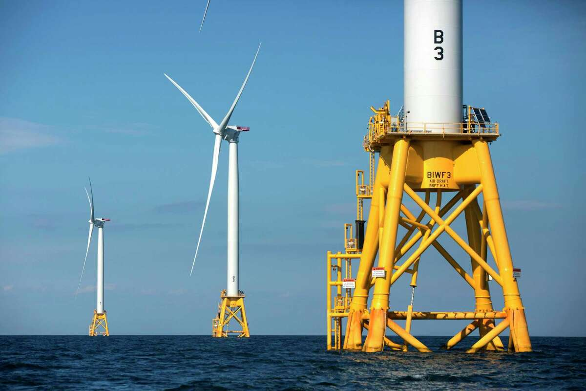 FILE - In this Aug. 15, 2016 file photo, three wind turbines from the Deepwater Wind project stand off Block Island, R.I. Ørsted U.S. Offshore Wind, a division of a Denmark-based developer, is opening a hub on Monday, March 2, 2020, in Providence, R.I., that its executives hope will help accelerate the takeoff of the industry in the United States. (AP Photo/Michael Dwyer, File)
