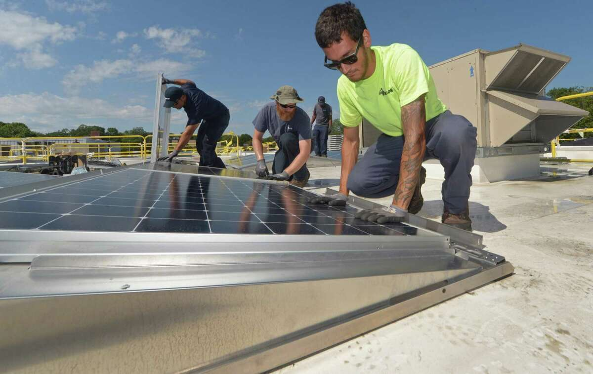 ENCON employees including C.J. Pappas, left, install solar panels on the roof of the Paul Miller Nissan dealership in Fairfield, which has installed the solar-energy array with financing from Darien-based Greenworks Lending, Wednesday, July 18, 2018, in Fairfield, Conn.