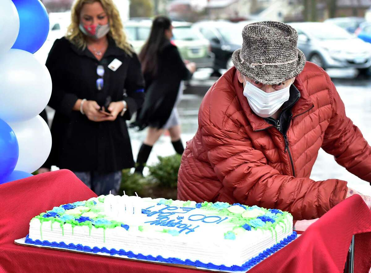Edward Otremba Sr., a resident at The Landing of North Haven assisted living facility, gets a 100th birthday celebration Friday practicing social distancing with a community car parade that included a North Haven Fire Department truck, the presentation of a birthday cake, and birthday songs in English and Polish.