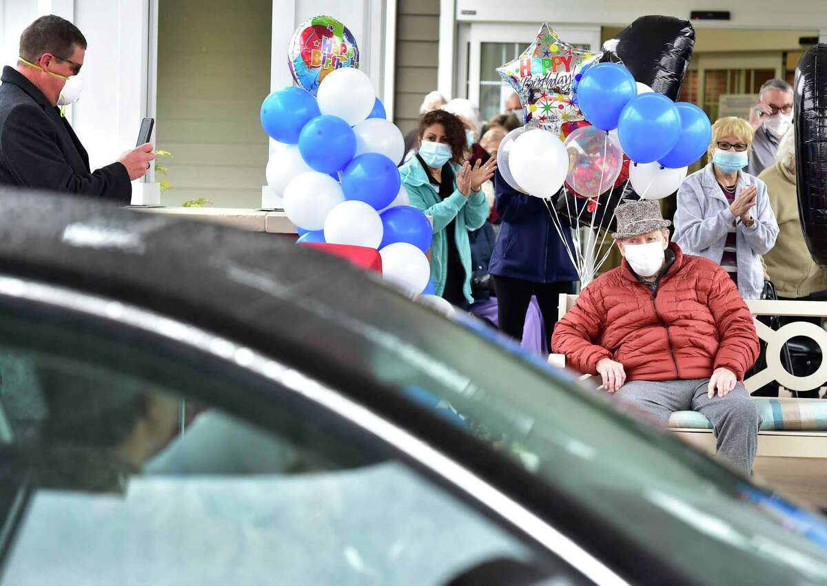 Edward Otremba Sr., a resident at The Landing of North Haven assisted living facility, seated, left, gets a 100th birthday celebrationFriday using social distancing with a community car parade that included a North Haven Fire Department truck, the presentation of a birthday cake, and birthday songs in English and Polish.