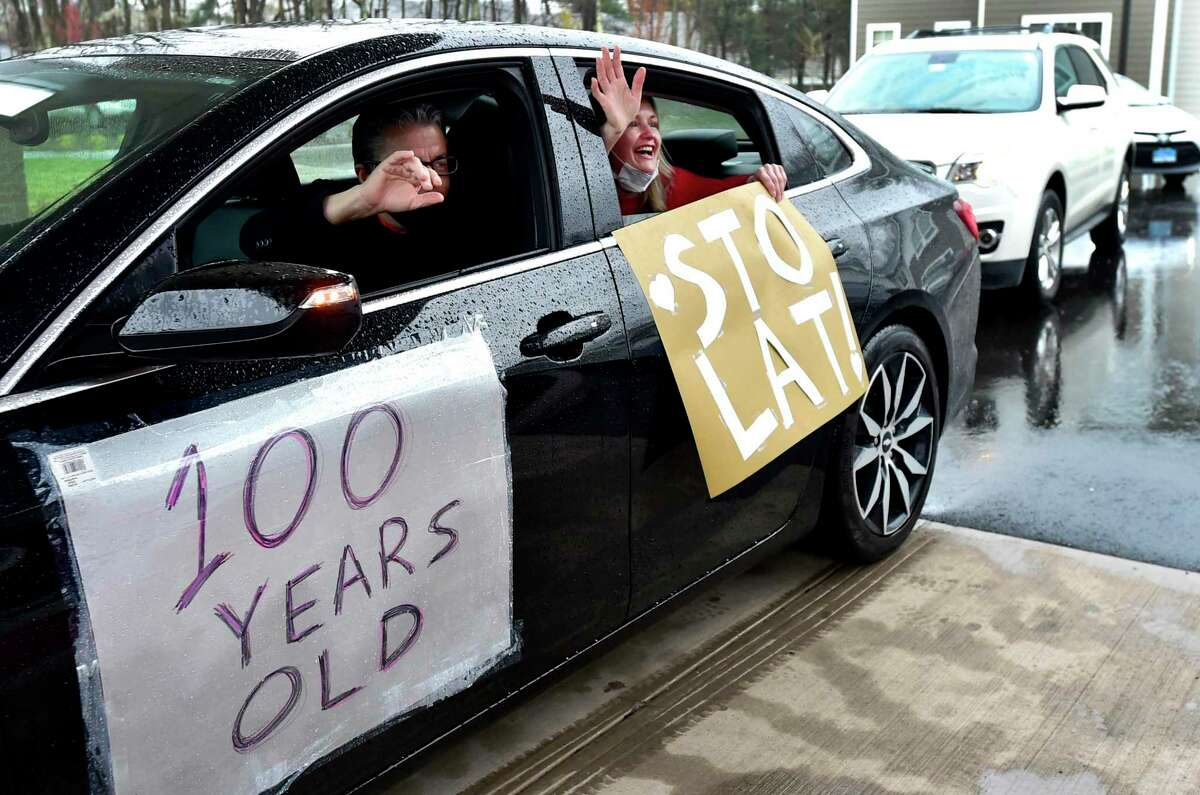 """Cathy DellaValle of Haven, right, holds a sign """"Sto lat,"""" the name of a Polish song that is sung to express good wishes, good health and long life to a person during a celebratory procession Friday honoring her father Edward Otremba Sr., a resident at The Landing of North Haven assisted living facility, during his 100th birthday party."""
