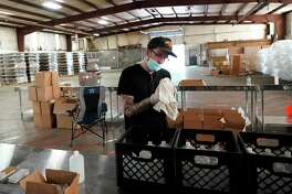 Bartender Tony Lamperti wipes a bottle of hand sanitizer while temporarily working at the William Price Distilling Company Thursday, April 23, 2020, in Houston. The company, which started making hand sanitizer to help fight the coronavirus, is hiring out-of-work bartenders to help during the COVID-19 outbreak
