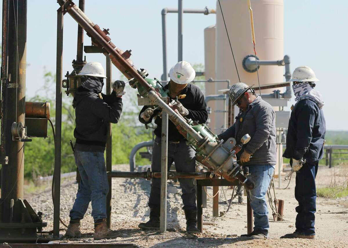 A contractor crew works on a flame arrestor for a flaring stack at an oil extraction site operated by Recoil Resources near Poth, Texas on Monday, Apr. 13, 2020. Recoil Resources and other small oil producers are struggling and are facing a plan to cut production by 20 percent if approved by the Railroad Commission.