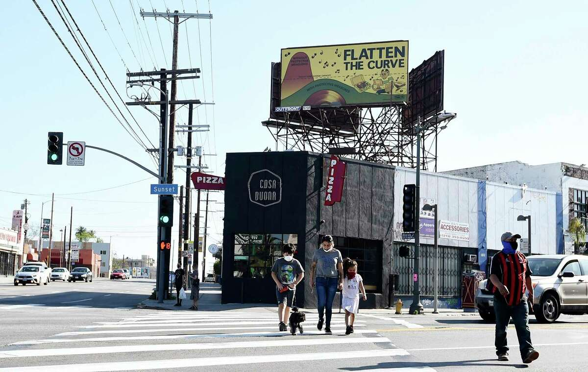 """Pedestrians cross the street underneath a billboard instructing citizens to """"flatten the curve"""" of coronavirus transmissions, Tuesday, April 21, 2020, in Los Angeles. (AP Photo/Chris Pizzello)"""