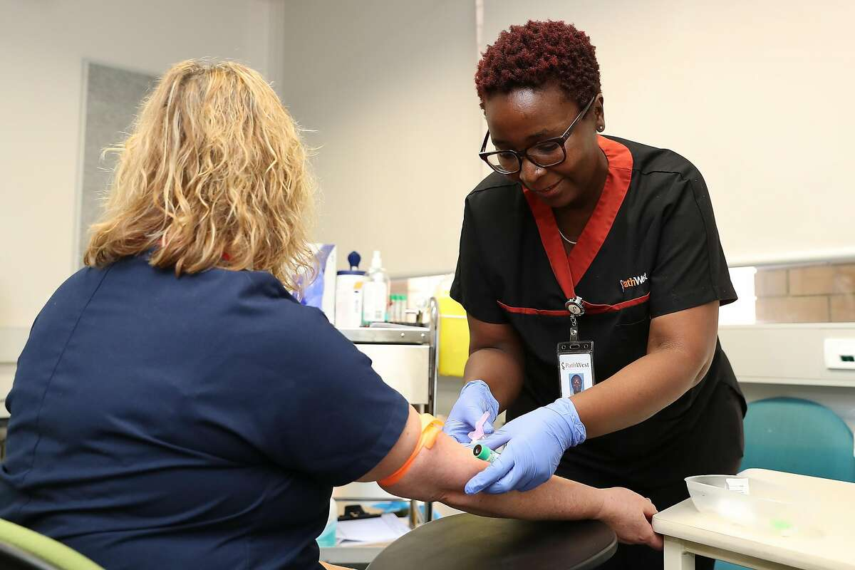 Clinical nurse has a blood sample taken by a clinical staff member at Sir Charles Gairdner hospital on April 20, 2020 in Perth, Australia.