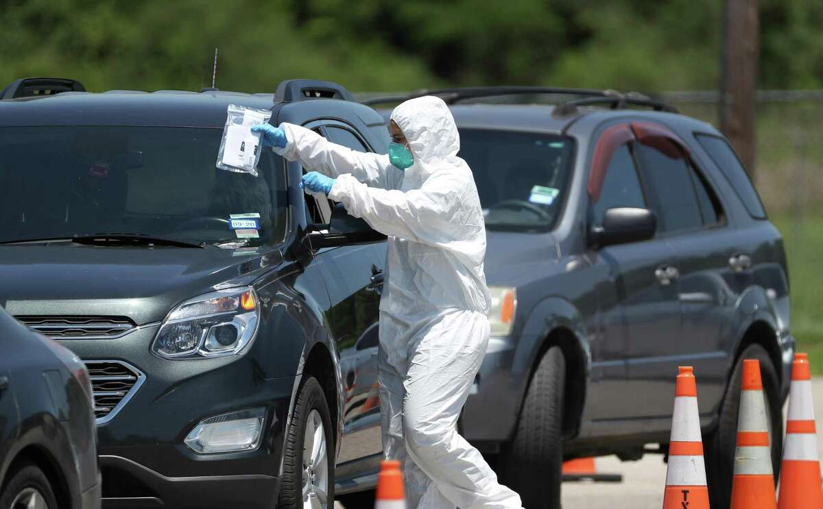 A worker places information on the windshield of a person wanting to get tested at a COVID-19 testing site located at 7525 Tidwell Friday, April 24, 2020, in Houston.