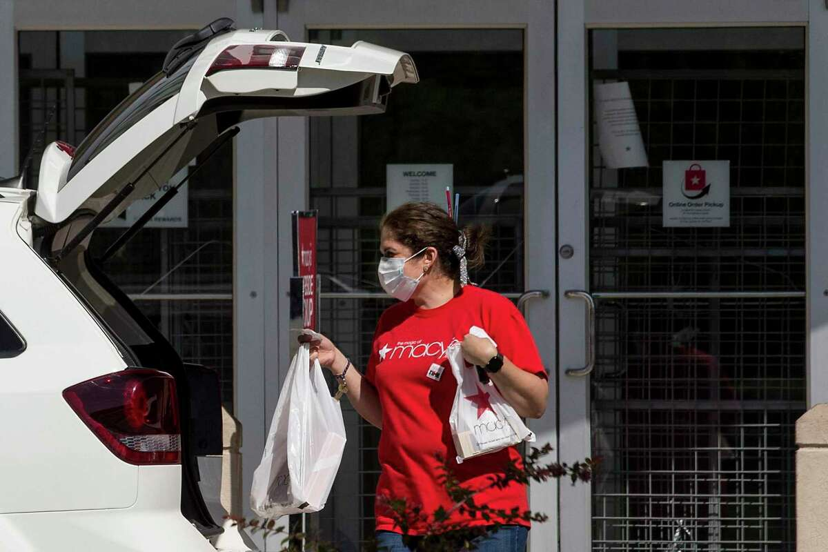 A Macy's employee makes a curbside delivery at The Woodlands Mall on Friday, April 24, 2020 in The Woodlands. Retail shops are beginning to re-open after being shut down because of the coronavirus pandemic, however, some high-risk or highly-exposed employees will be able to refuse work and continue to receive unemployment benefits.