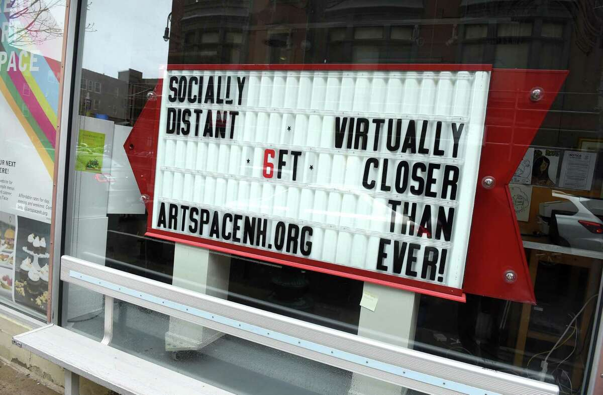A sign in the window of Artspace at the corner of Orange Street and Crown Street in New Haven advertises social distancing and their virtual presence on April 24, 2020.