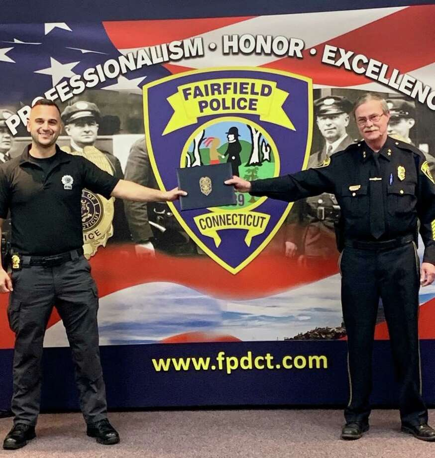 Chief Christopher Lyddy presented Detective Michael Clark with an award for distinguished service on Tuesday, April 21., 2020. Due to social distancing restriction, the chief and detective are standing a safe distance apart. Photo: Contributed Photo / Fairfield Police Department