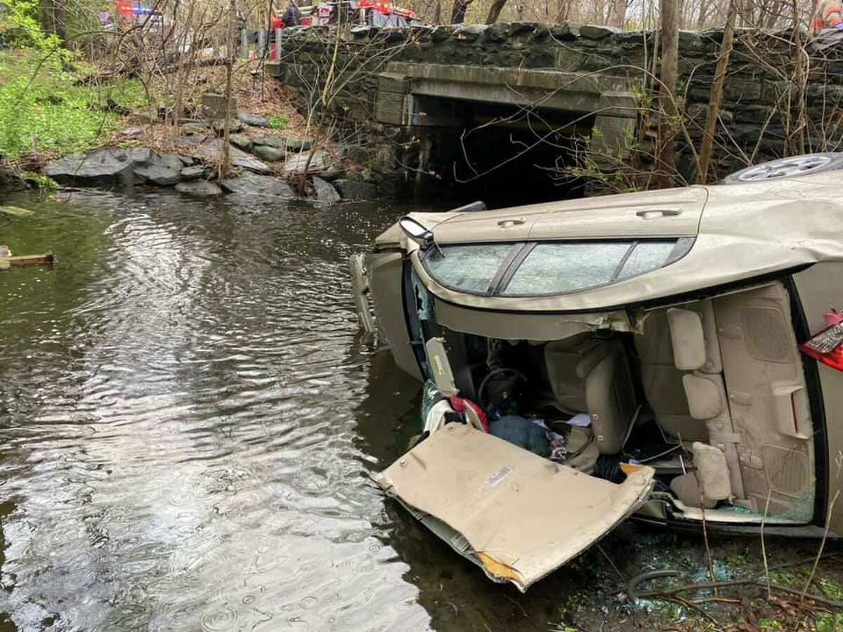 A vehicle down an embankment and in water off Glenville Road in Greenwich, Conn., on April 24, 2020. Firefighters had to remove the roof using the Jaws of Life to extricate the driver, who was trapped after the crash.
