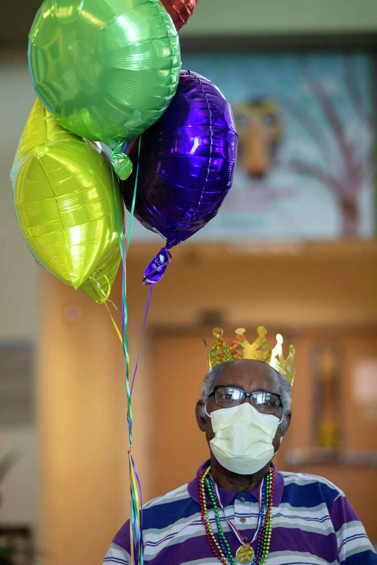 Allee Wallace, 85, holds balloons and sports a crown as he's discharged from a long-term acute care hospital.
