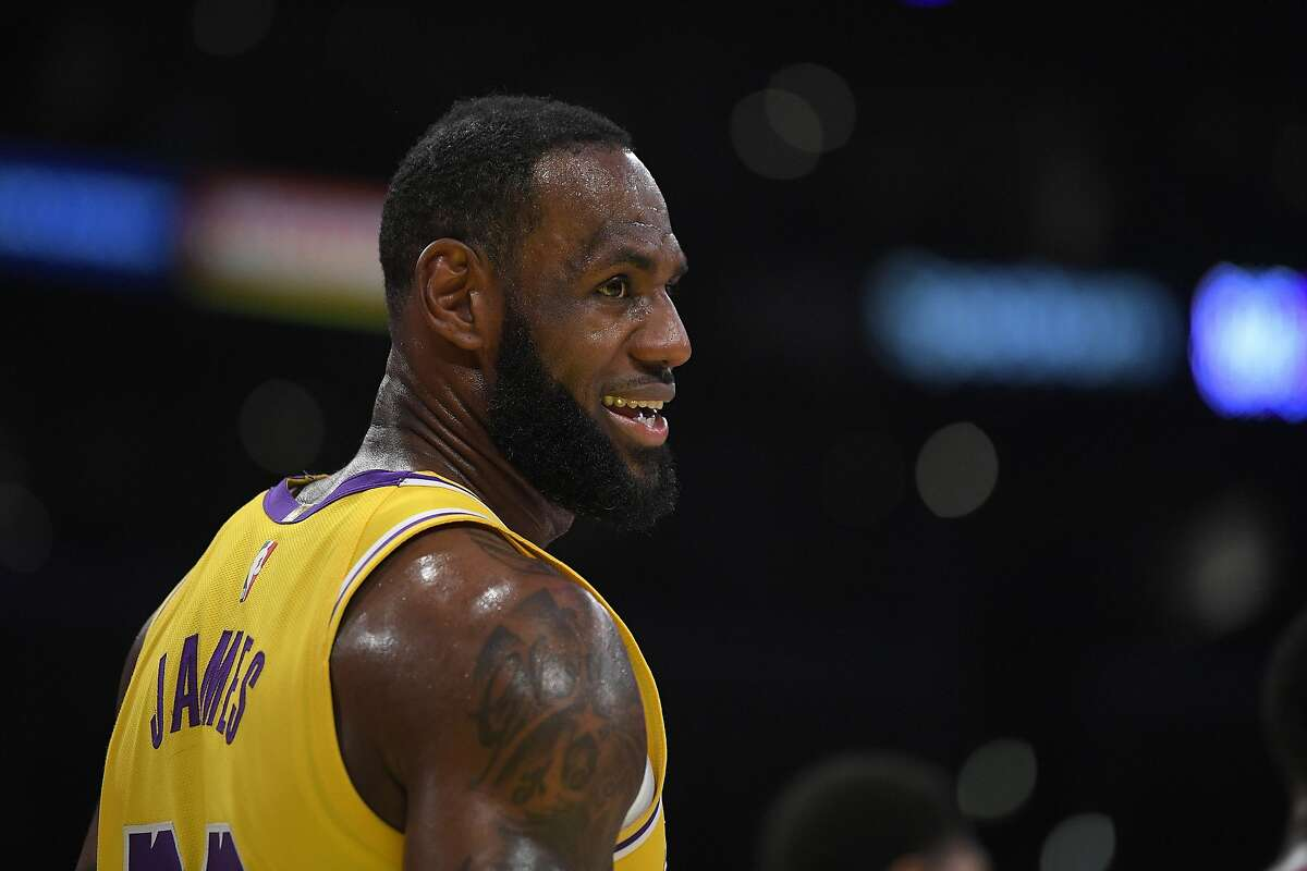 Los Angeles Lakers forward LeBron James smiles as he stands on the court during the first half of an NBA basketball game against the Philadelphia 76ers Tuesday, March 3, 2020, in Los Angeles. (AP Photo/Mark J. Terrill)