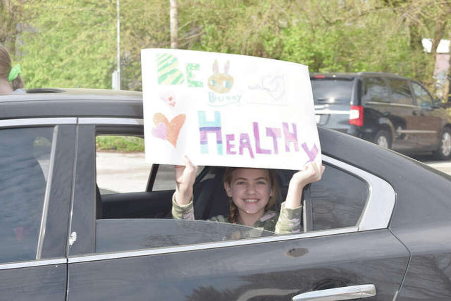 Brooklyn Walker, 10, the daughter of Brandy and Jud Walker of Jacksonville, holds a sign Friday during the Honks for Hugs parade. The parade visited several Jacksonville health care facilities. Photo: Samantha McDaniel-Ogletree | Journal-Courier