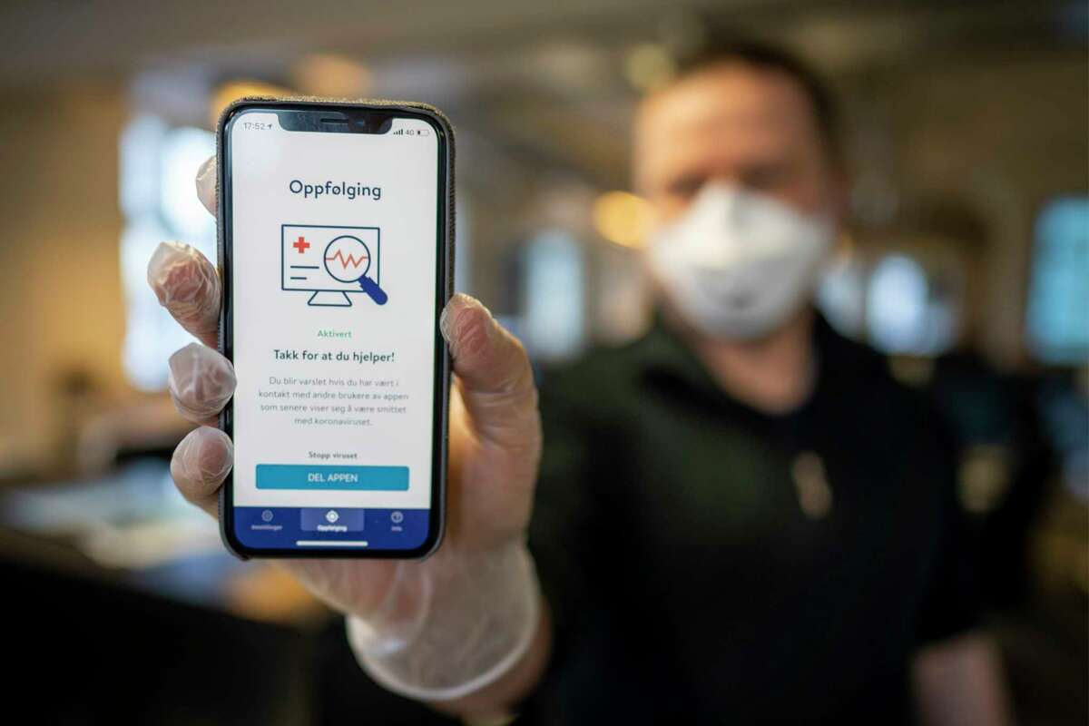 A man holds a mobile phone showing Norway's National Institute of Public Health new mobile app infection stop for infection tracking, in Oslo, Norway, Friday April 17, 2020. The app is intended to help authorities with infection detection, but can also be used for an alert if the user has been close to someone confirmed infected with the COVID-19 coronavirus. (Heiko Junge / NTB scanpix via AP)