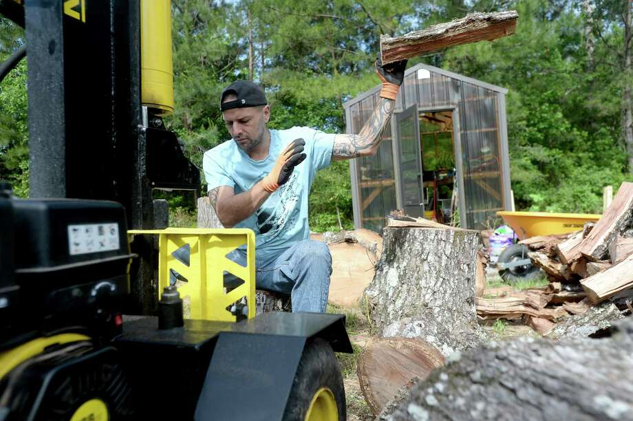 """Josh Duncan splits wood from a cut red oak tree at Larry Shaw's home in Lumberton Monday, April 20, with help from his Reel Cajun restaurant co-worker Jamal Brown. Duncan has had a firewood side business, one of many he has developed over time, but is now relying on its income to help support he and teen son Jacob, since he and fellow restaurant workers were let go following restaurant closures amid COVID-19 restrictions. """"I'm just a single father trying to make it,"""" he says. Everyday he hustles to make ends meet, as calls to apply for unemployment have proved fruitless. Photo taken Monday, April 20, 2020 Kim Brent/The Enterprise Photo: Kim Brent / The Enterprise / BEN"""